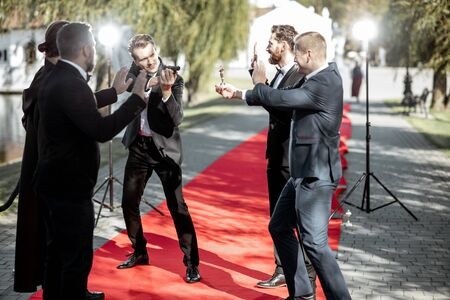 Group of a men as a well-known movie actors and secret agent playing with handgun during awards ceremony on the red carpet outdoors