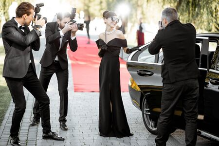 Hermosa mujer vestida con estilo retro como una famosa actriz de cine que llega a la ceremonia de entrega de premios con reporteros fotográficos que le toman fotografías.