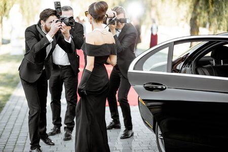 Schöne Frau im Retro-Stil als berühmte Filmschauspielerin gekleidet, die bei der Preisverleihung ankommt, während Fotoreporter Bilder von ihr machen