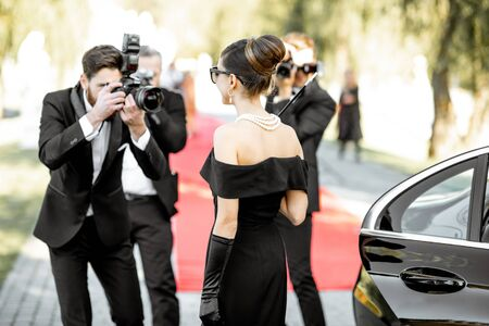 Beautiful woman dressed in retro style as a famous movie actress arriving on the awards ceremony with photo reporters taking pictures of her
