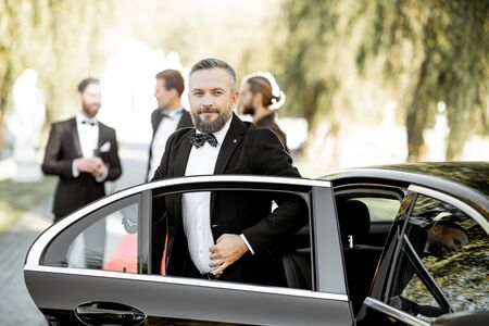 Man as a famous movie actor getting out the luxury car, arriving on the awards ceremony or movie premiere outdoors