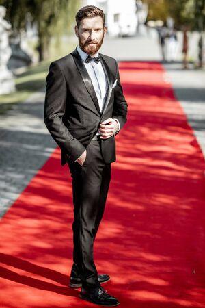 Full body portrait of an elegant man strictly dressed in tuxedo posing on the red carpet outdoors 版權商用圖片
