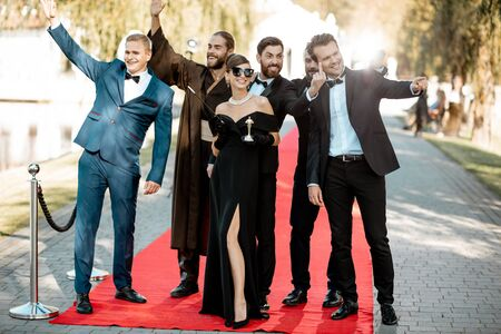 Group portrait of an elegant people as a famous movie actors standing together on the red carpet during awards ceremony outdoors Stockfoto - 133006810