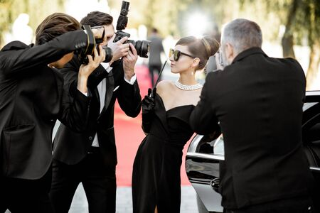 Beautiful woman dressed in retro style as a famous movie actress arriving on the awards ceremony with annoying photo reporters taking pictures of her