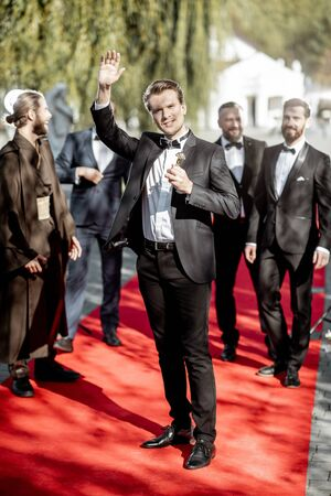 Portrait of an elegant man as a well-known movie actor holding famous Academy Award during awards ceremony on the red carpet outdoors