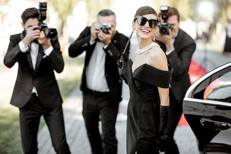 Hermosa mujer vestida con estilo retro como una famosa actriz de cine que llega a la ceremonia de entrega de premios con reporteros fotográficos que le toman fotografías. Foto de archivo