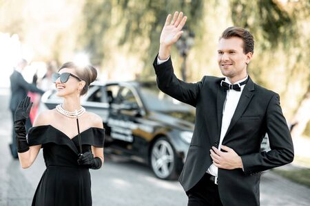 Elegant man and woman as a famous movie actors walking together during awards ceremony outdoors Stock Photo