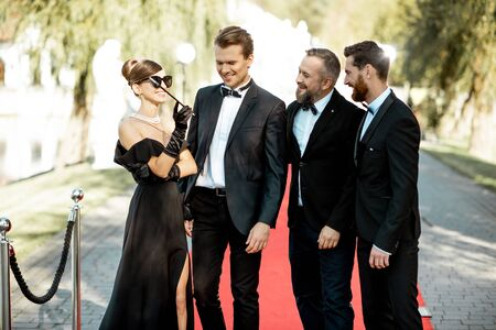 Group portrait of a elegant people as a famous movie actors standing together on the red carpet during awards ceremony outdoors 版權商用圖片