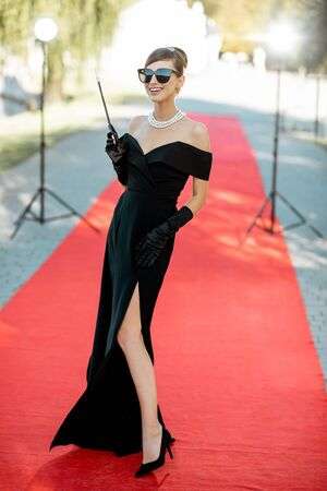 Portrait of a beautiful woman dressed in retro style as a famous movie actress on the red carpet during awards ceremony outdoors Stock Photo