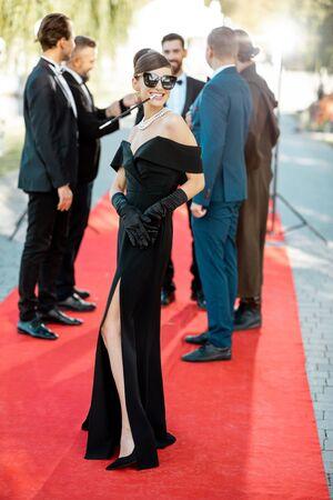 Ritratto di una bella donna vestita in stile retrò come una famosa attrice cinematografica sul tappeto rosso durante la cerimonia di premiazione all'aperto Archivio Fotografico