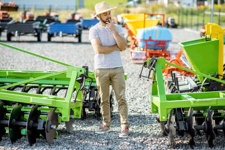Portrait of a thoughtful agronomist standing near the plow at the outdoor ground of the shop, choosing new agricultural machinery for farming