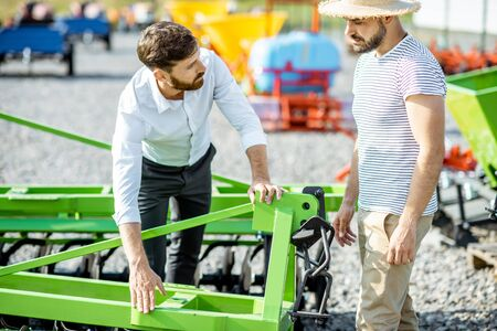 Young agronomist with salesman or manager at the open ground of the shop with agricultural machinery, buying a new plow for tillage 스톡 콘텐츠