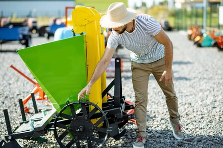 Agronomist choosing a new planter for farming at the outdoor ground of the shop with agricultural machinery Stockfoto - 133055152