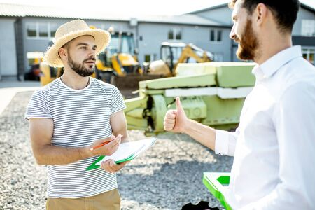 Young agronomist with salesman or manager at the open ground of the shop with agricultural machinery