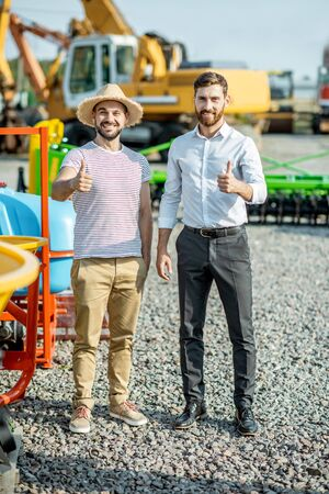 Young agronomist with salesman at the open ground of the shop with agricultural machinery, buying a new planter for farming Stockfoto - 133040244