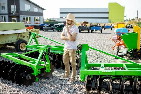 Portrait of a thoughtful agronomist standing near the plow at the outdoor ground of the shop, choosing new agricultural machinery for farming Stock Photo - 132940111
