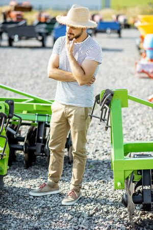 Portrait of a thoughtful agronomist standing near the plow at the outdoor ground of the shop, choosing new agricultural machinery for farming Stock Photo - 133053744