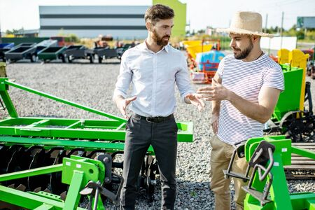 Young agronomist with salesman or manager at the open ground of the shop with agricultural machinery, buying a new plow for tillage Stock Photo