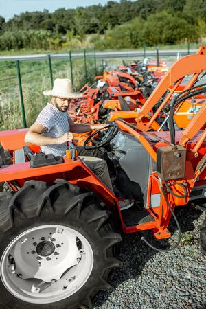 Young agronomist trying tractor for farming, choosing agricultural machinery on the open ground of the shop