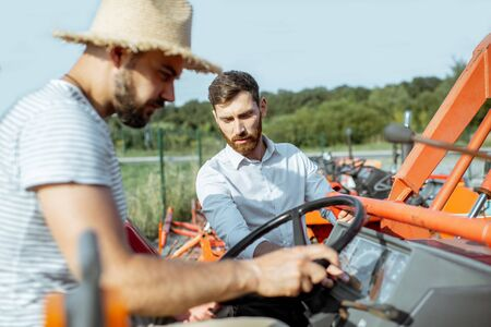 Young agronomist with elegant salesman choosing a tractor for farming on the open ground of agricultural shop Stockfoto