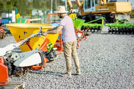Agronomist choosing farm cultivator machine at the outdoor ground of the shop with agricultural machinery