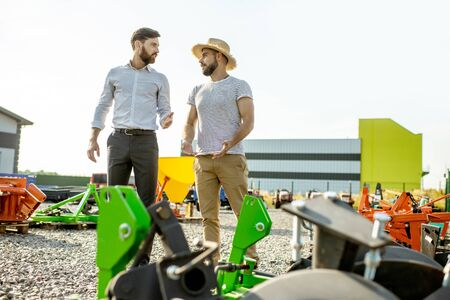 Young agronomist walking with salesman at the open ground of the shop with agricultural machinery, choosing new plow for tillage