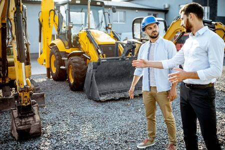 Builder choosing heavy machinery for construction with a sales consultant on the open ground of a shop with special vehicles Stock Photo - 133053256