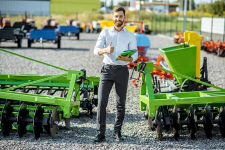 Portrait of a handsome salesman standing near the plow at the outdoor ground of the shop with new agricultural machinery 스톡 콘텐츠