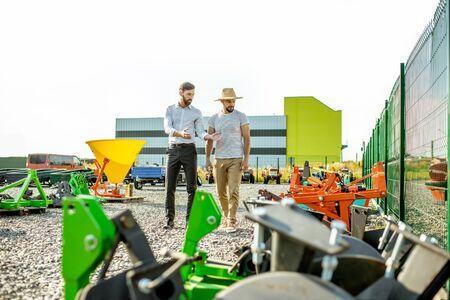 Junger Agronom, der mit Verkäufer auf dem offenen Gelände des Ladens mit Landmaschinen spazieren geht und einen neuen Pflug für die Bodenbearbeitung wählt