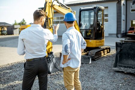 Builder choosing heavy machinery for construction with a sales consultant on the open ground of a shop with special vehicles