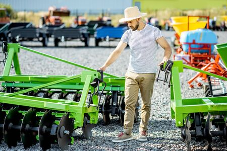 Agronomist choosing a new plow for farming at the outdoor ground of the shop with new agricultural machinery 스톡 콘텐츠