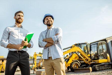 Baumeister, der schwere Maschinen für den Bau mit einem Verkaufsberater auswählt, der mit einigen Dokumenten auf dem offenen Gelände eines Ladens mit Spezialfahrzeugen steht