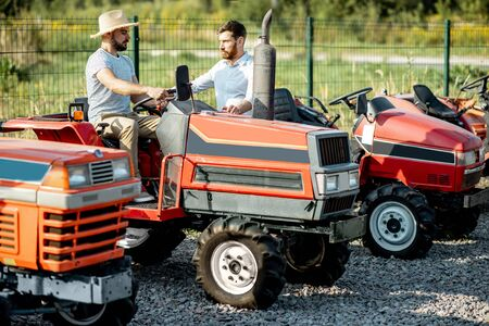 Young agronomist with elegant salesman choosing a tractor for farming on the open ground of agricultural shop