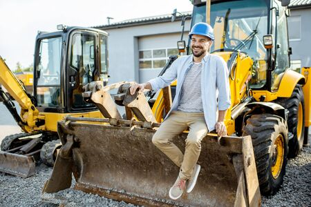 Portrait of a handsome builder sitting on a bulldozer scoop on the open ground of the shop with heavy machinery