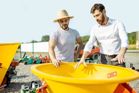 Young agronomist with salesman at the open ground of the shop with agricultural machinery, buying a new planter for farming