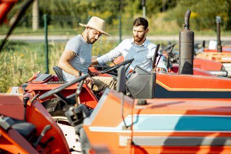 Jonge agronoom met elegante verkoper die een tractor kiest voor landbouw op de open grond van een landbouwwinkel