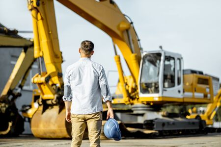 Portrait of a handsome builder standing back on the open ground of the shop with heavy machinery for construction Stock Photo