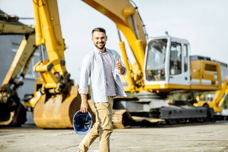 Portrait of a handsome builder standing on the open ground of the shop with heavy machinery for construction Stock Photo