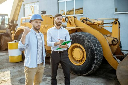 Builder choosing heavy machinery for construction with a sales consultant, signing some documents on the open ground of a shop with special vehicles Stock Photo