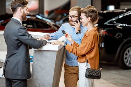 Sales manager with a young couple buying a new car, standing with documents and dealing some formal things at the car dealership