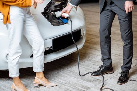 Sales manager showing how to charge electric car to a young client, plugging wire into the car socket at the car dealership. Close-up view with no face