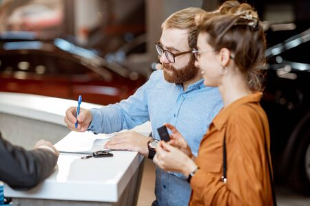 Giovane coppia che firma alcuni documenti, acquistando una nuova auto nel moderno showroom della concessionaria auto