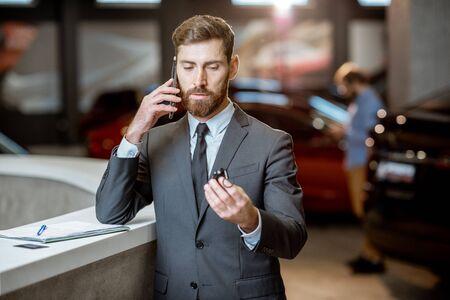 Ritratto di un felice direttore delle vendite o uomo d'affari che parla con il telefono e si sente entusiasta di vendere o acquistare una nuova auto Archivio Fotografico