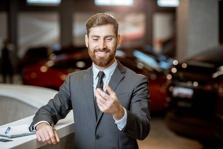 Ritratto di un felice responsabile delle vendite o uomo d'affari che tiene in mano la chiave dell'auto, entusiasta di vendere o acquistare una nuova auto presso il concessionario auto