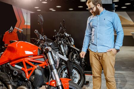 Man choosing a motorcycle to buy, looking on the plate with specifications and price in the showroom with expensive sports bikes Reklamní fotografie - 133046851