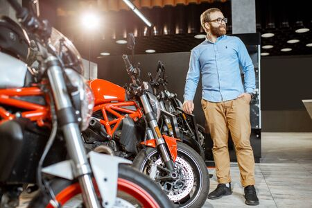 Man choosing a motorcycle to buy in the showroom with expensive sports bikes