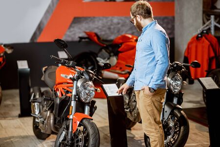 Man choosing a motorcycle to buy, looking on the plate with specifications and price in the showroom with expensive sports bikes Reklamní fotografie