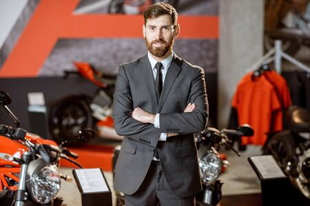 Portrait of a confident sales manager in the suit selling sports motorcycles in the showroom 免版税图像