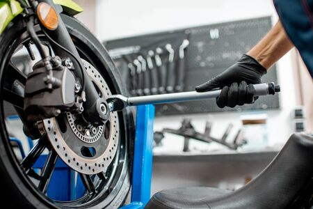 Mechanic tightening motorcycle wheel with a hand wrench during a repairment at the workshop, close-up view 版權商用圖片