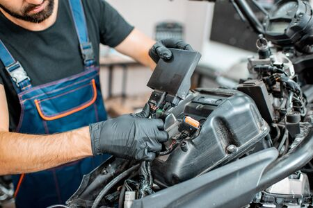 Electrician or repairman in protective gloves connecting wiring in the motorcycle during a repairment at the workshop